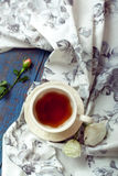 Cup of tea set with a beautiful tea towel and roses on a wooden Royalty Free Stock Photo