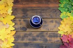 A cup of tea among a set of yellowing fallen autumn leaves on a background surface of natural wooden boards of dark brown colo. R royalty free stock image