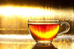 Cup of tea on shiny gold background Royalty Free Stock Images