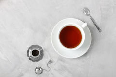Cup of tea silver spoon little teapot on concrete background. Stock Images