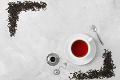 Cup of tea silver spoon little teapot on concrete background. Stock Photos