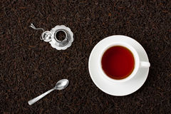Cup of tea silver spoon little teapot on leaves background. Stock Photography