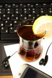 A Cup of tea with a slice of lemon on the background of laptop Stock Photos