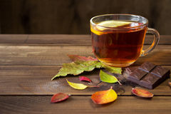 Cup of tea with slice of lemon and chocolate with autumn leaves on old wooden table. Royalty Free Stock Photos