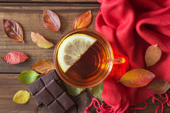 Cup of tea with slice of lemon and chocolate with autumn leaves on old wooden table. Royalty Free Stock Photography