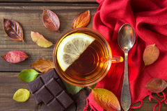 Cup of tea with slice of lemon and chocolate with autumn leaves on old wooden table. Stock Images