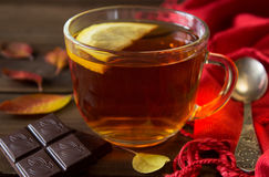Cup of tea with slice of lemon and chocolate with autumn leaves on old wooden table. Stock Photo