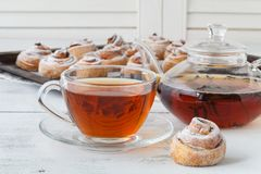 Cup of tea and small apple roses shaped pies. Sweet apple desser Stock Image