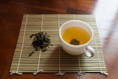 Cup of tea on small bamboo mat with dried tea leaves Stock Photo