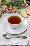 Cup of tea and small cakes. On wooden rustic table. Party dessert Stock Photo