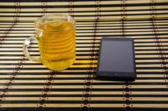The cup of tea and smartphone on a bamboo mat Royalty Free Stock Photography