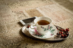 Cup of tea and smartphone, home relaxation Stock Images