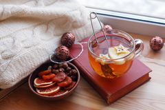 Cup of tea, snacks, book and warm blanket on windowsill, close up, relax unplug background, seasonal homely weekend, love to read. Concept stock images
