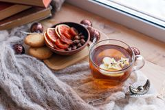 Cup of tea, snacks, book and warm blanket on windowsill, close up, relax unplug background, seasonal homely weekend, love to read. Concept stock photos