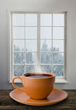 A cup of tea and snowstorm. View from the window on the background Royalty Free Stock Images