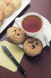 A cup of tea and some chocolate chip cookies on a brown wooden. A tea and some chocolate chip cookies on a brown wooden table stock photo