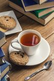 A cup of tea and some chocolate chip cookies over a books on a brown wooden table. Vintage style royalty free stock photography