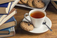 A cup of tea and some chocolate chip cookies over a books on a brown wooden table. Vintage style royalty free stock images