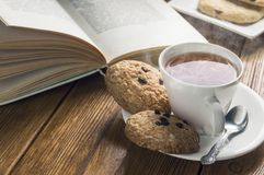 A cup of tea and some chocolate chip cookies over a books on a brown wooden table. Vintage style stock photos