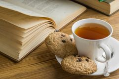 A cup of tea and some chocolate chip cookies over a books on a brown wooden table. Vintage style stock images