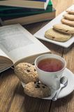 A cup of tea and some chocolate chip cookies over a books on a brown wooden table. Vintage style stock image