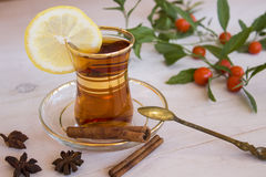 Cup of tea with spices and lemon. And a sprig of nightshade flower Stock Images