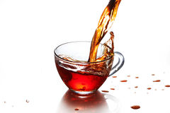 Cup of tea with splash isolated. On the white background Royalty Free Stock Photos