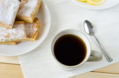 Cup of tea with spoon and lemon bars. Cup of tea with a spoon and lemon bars Royalty Free Stock Photography