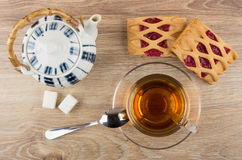 Cup with tea, spoon, lumpy sugar, teapot and pies Royalty Free Stock Images