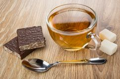 Cup of tea, spoon, lumpy sugar, teaspoon and broken wafer. In chocolate on wooden table Stock Image