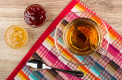Cup of tea and spoon on napkin, bowls with jam Stock Photos