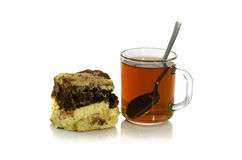 Cup of tea with a spoon and a piece of cake. On white background Royalty Free Stock Images
