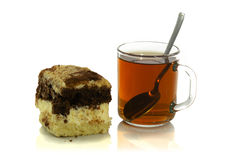 Cup of tea with a spoon and a piece of cake. On white background Stock Photos
