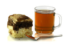 Cup of tea with a spoon and a piece of cake. On white background Stock Images