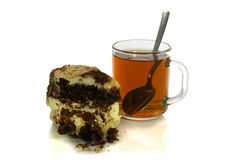 Cup of tea with a spoon and a piece of cake. On white background Royalty Free Stock Photo