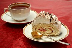 Cup of tea with the spoon and a slice of pie on red background royalty free stock images