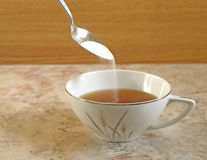 Cup of Tea. Spoon of sugar pouring into cup of tea Stock Image