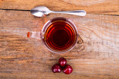 Cup of tea, spoon and sweet cherry on a wooden background Royalty Free Stock Image