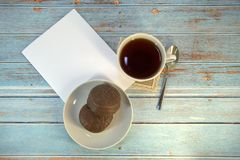 A cup of tea, a spoon, two chocolate cakes on a plate and a sheet of paper on a wooden table royalty free stock photos