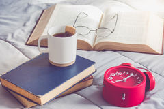 A cup of tea on stack book with open book  and red alarm clock o Royalty Free Stock Photography
