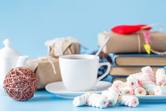Cup of tea with stack of books with twisted marshmallow Stock Images