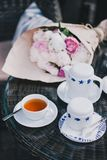Cup of tea standing near teapot and sugar bowl. In front of bouquet of peonies Stock Photo