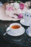 Cup of tea standing near teapot and sugar bowl. In front of bouquet of peonies Stock Photos