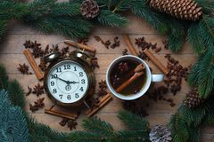 Cup of tea with star anise and cinnamon with alarm clock Stock Images