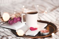 Valentines day with cup of tea in bed. Cup of tea staying on open book with flowers and lights at background. Valentines day. Good morning royalty free stock photos