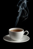 Cup of tea with steam. Isolated over black background Stock Photography