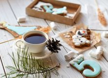 A cup of tea, sticks with sugar cristals, marshmallows and some elements of Christmas decor on a white wooden surface. A cup of tea, sticks with sugar cristals Royalty Free Stock Photography