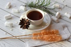 A cup of tea, sticks with sugar cristals, marshmallows and some elements of Christmas decor. On a white wooden surface stock photos