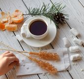 A cup of tea, sticks with sugar cristals, marshmallows and some elements of Christmas decor. On a white wooden surface stock image