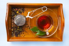 Cup of tea and a tea strainer. On a brown wooden tray. Brewing tea Royalty Free Stock Photo